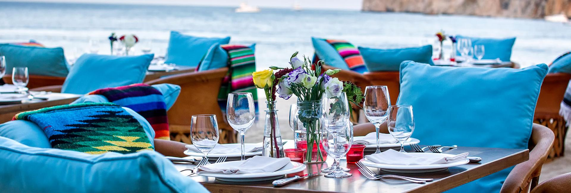 Chairs and tables set for dinner by the ocean